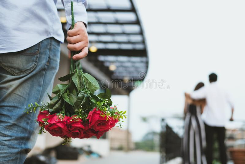 Hombre afligido que sostiene el ramo de rosas rojas que sienten tristes mientras que s imagen de archivo libre de regalías