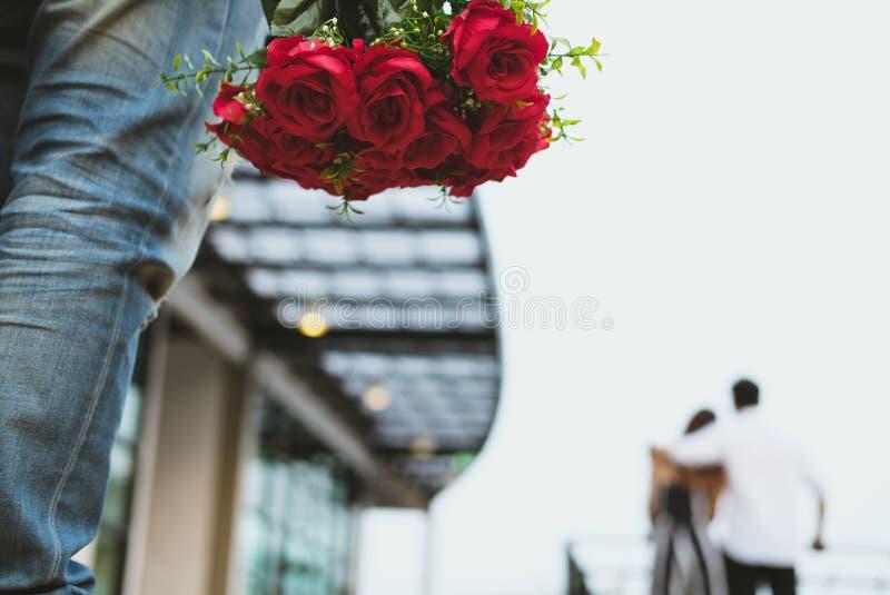 Hombre afligido que sostiene el ramo de rosas rojas que sienten tristes mientras que s foto de archivo libre de regalías