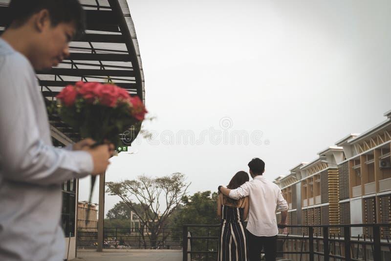 Hombre afligido que sostiene el ramo de rosas rojas que sienten tristes mientras que s imágenes de archivo libres de regalías