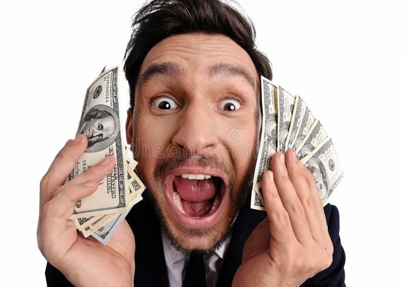 Hombre afortunado que sostiene el dinero de 100 billetes de dólar en su mano fotos de archivo