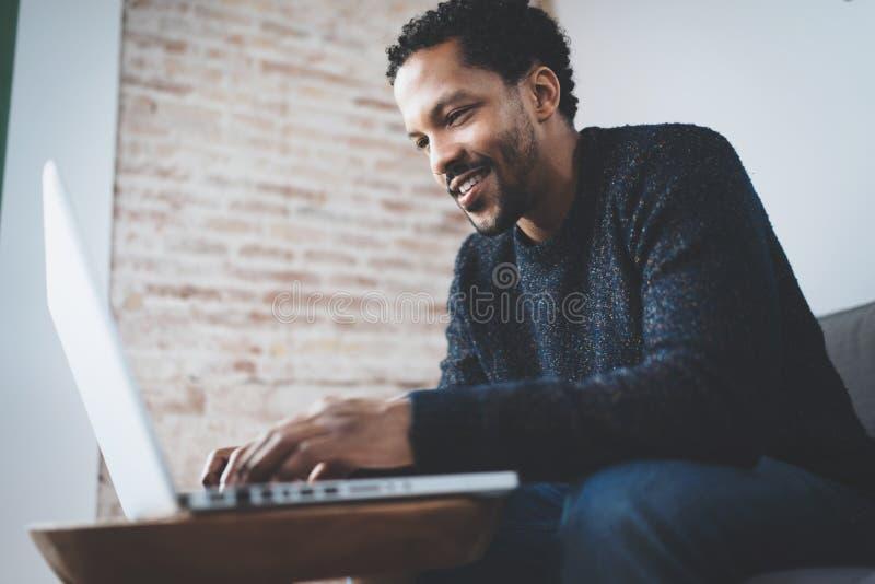 Hombre africano alegre que usa el ordenador y sonriendo mientras que se sienta en el sofá Concepto de hombres de negocios jovenes foto de archivo