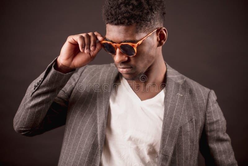 Hombre africano apuesto en gafas de sol elegantes, chaqueta del traje y la camiseta blanca foto de archivo