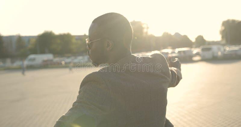 Hombre africano atractivo confiado en ropa de moda y gafas de sol que dan vuelta a la ronda, señalando en la cámara con los finge imagenes de archivo