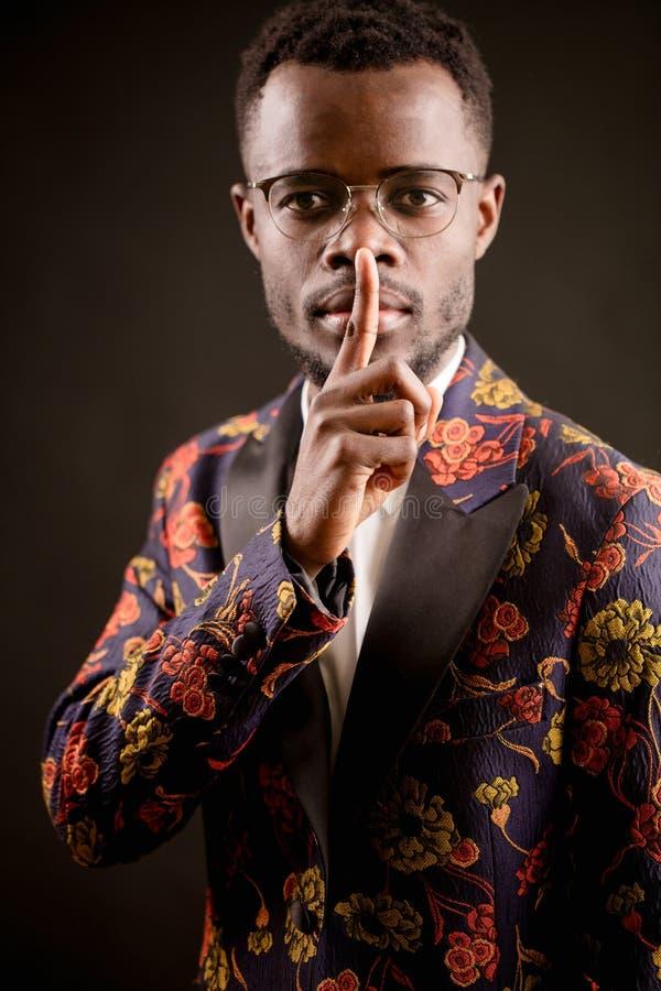 Hombre africano atractivo en la chaqueta de moda del traje que hace gesto del silencio fotos de archivo