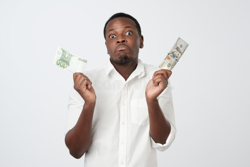 Hombre africano atractivo joven que lleva a cabo la moneda de los E.E.U.U. y la moneda del euro que deciden cuál para elegir imagen de archivo libre de regalías
