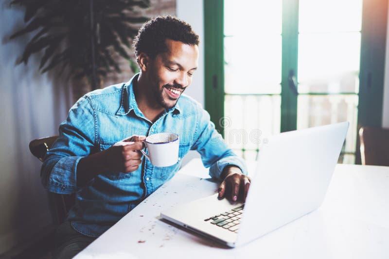 Hombre africano barbudo feliz que trabaja en casa mientras que sienta la tabla de madera Usando el ordenador portátil moderno par imágenes de archivo libres de regalías