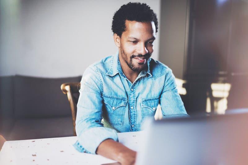 Hombre africano barbudo sonriente que trabaja en el ordenador portátil mientras que pasa tiempo en la oficina coworking Concepto  fotografía de archivo