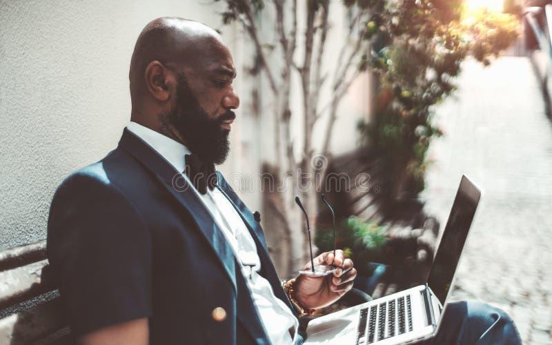 Hombre africano con el ordenador port?til al aire libre imagen de archivo