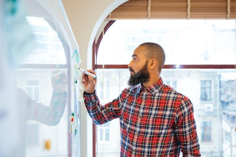 Hombre africano con la situación y la escritura de la barba en whiteboard imágenes de archivo libres de regalías