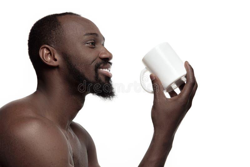 Hombre africano con la taza de té, aislada en el fondo blanco imagenes de archivo