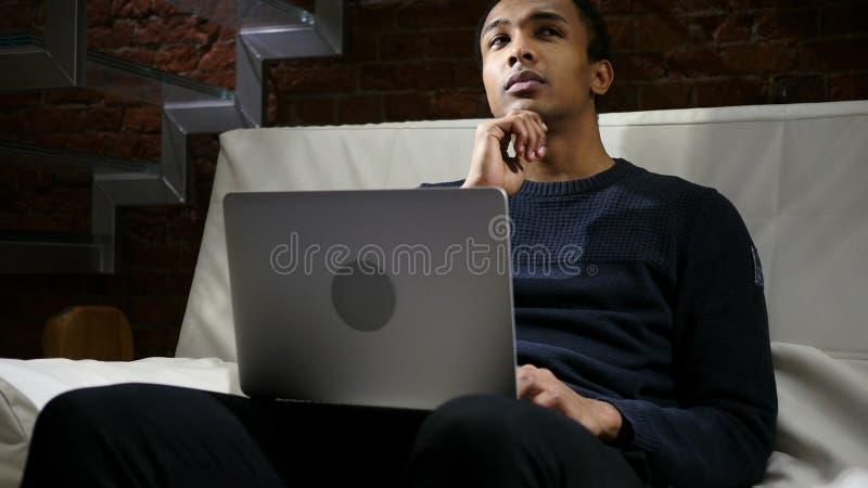 Hombre africano de pensamiento pensativo que trabaja en el ordenador portátil en la noche imágenes de archivo libres de regalías