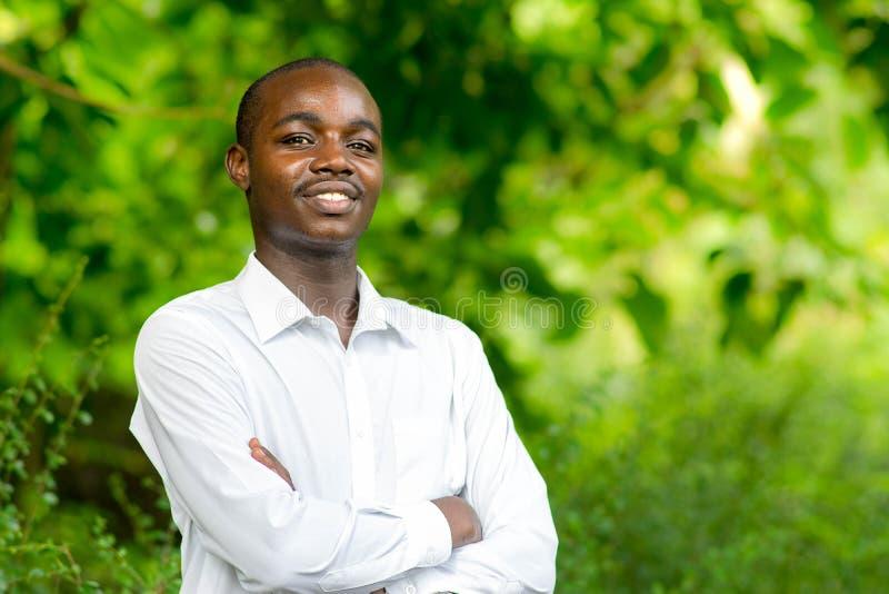 Hombre africano del retrato de la sonrisa en fondo verde de la naturaleza foto de archivo libre de regalías