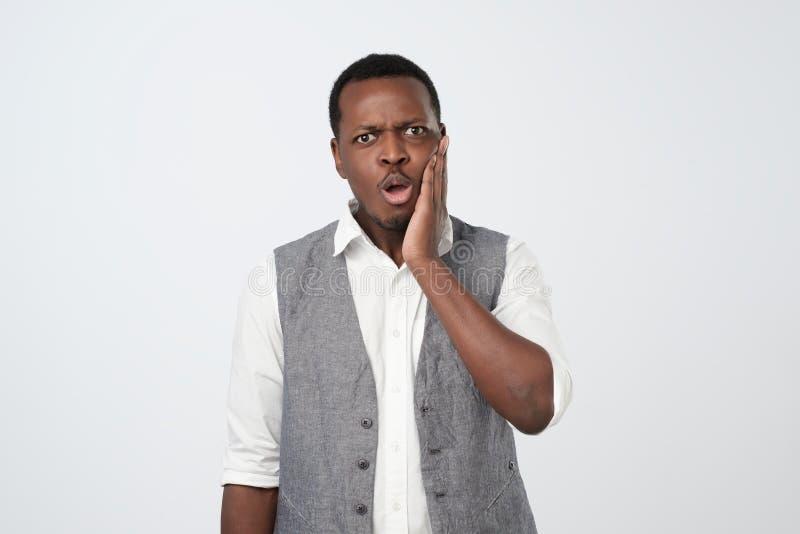 Hombre africano desconcertado o sorprendido vestido en la camisa blanca y el chaleco que miran en choque y la frustración imágenes de archivo libres de regalías