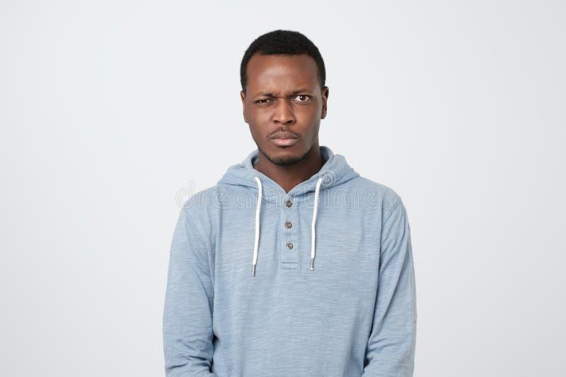 Hombre africano dudoso en el pulover azul que mira con la expresión de la incredulidad fotografía de archivo libre de regalías