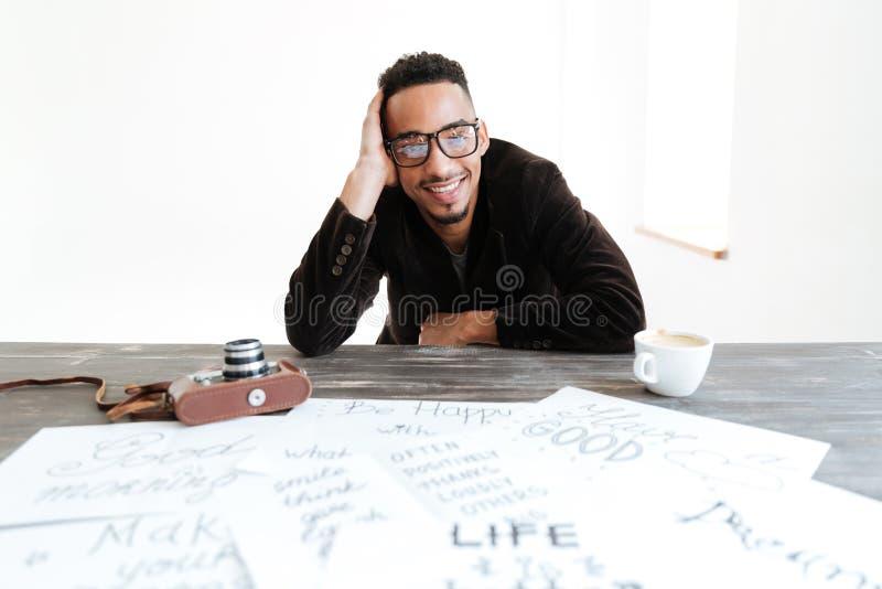 Hombre africano en el traje que se sienta por la tabla fotografía de archivo libre de regalías