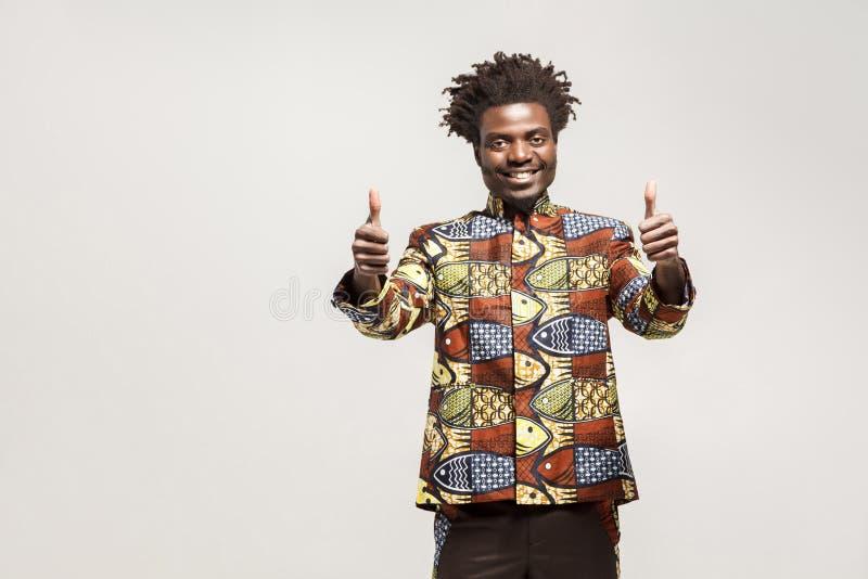Hombre africano en la ropa tradicional sonrisa dentuda, mostrando los pulgares foto de archivo