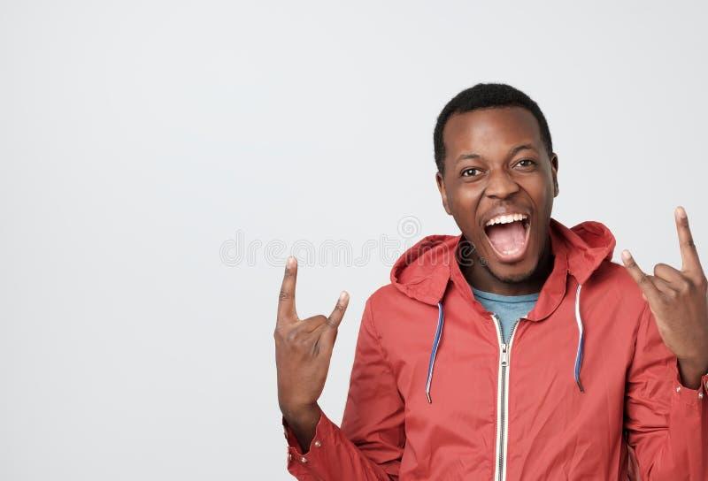 hombre africano en ropa roja que grita y que grita, feliz, sensación grande Mostrándola a roca para firmar fotografía de archivo