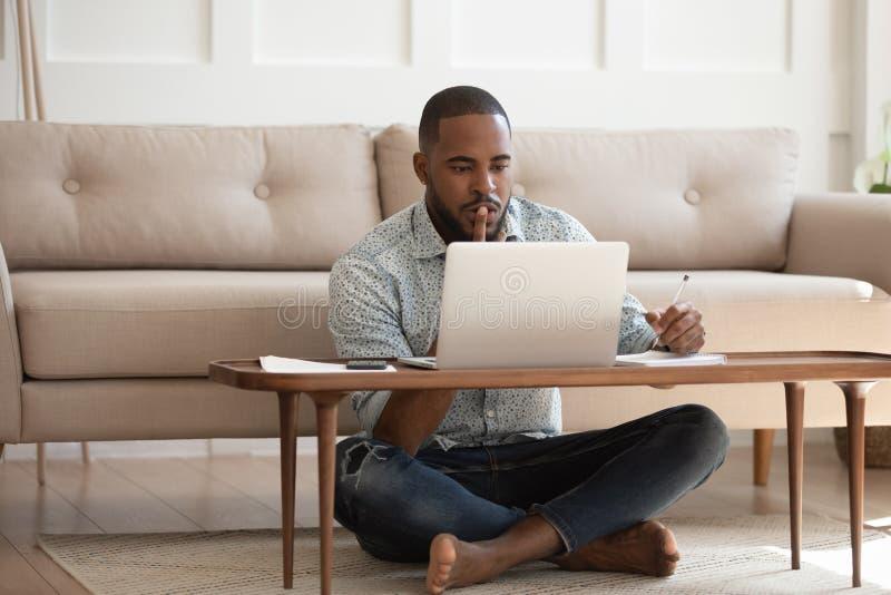 Hombre africano enfocado que estudia o que trabaja en el ordenador portátil en casa foto de archivo libre de regalías