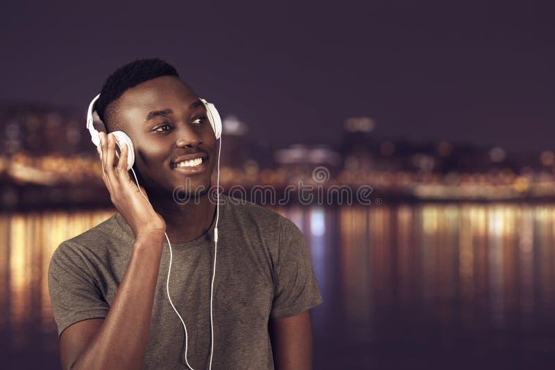 Hombre africano feliz que camina en la playa mientras que música que escucha con los auriculares fotos de archivo