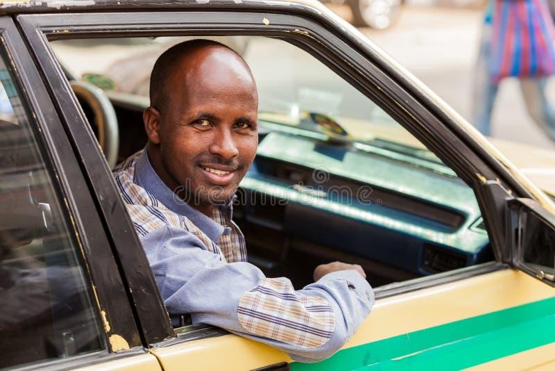 Hombre africano feliz que se sienta en un taxi, sonriendo derecho en la leva fotografía de archivo