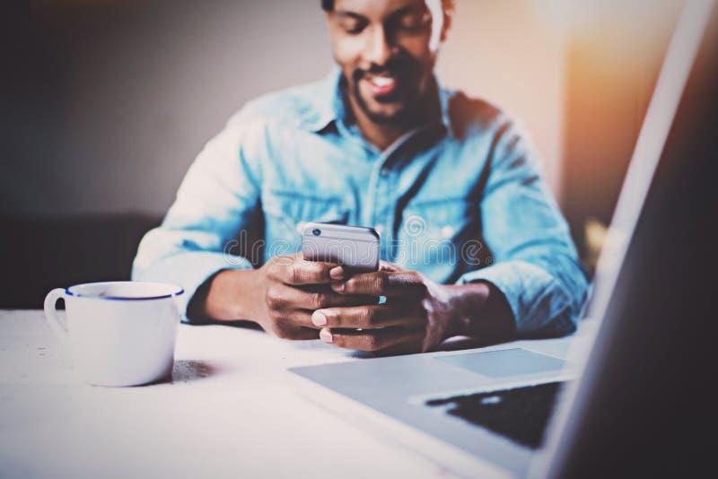 Hombre africano feliz que usa smartphone mientras que sienta en la tabla de madera su hogar moderno Concepto de trabajo de la gen foto de archivo libre de regalías