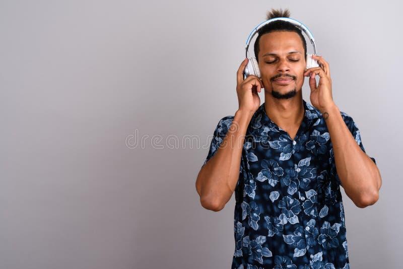Hombre africano hermoso barbudo joven que escucha la música contra GR foto de archivo libre de regalías