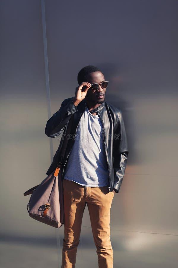 Hombre africano hermoso en la chaqueta de cuero y gafas de sol foto de archivo