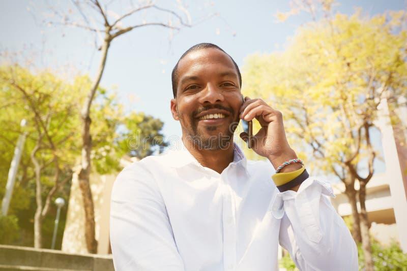 Hombre africano hermoso joven que habla en smartphone mientras que se sienta en el parque soleado de la ciudad foto de archivo libre de regalías