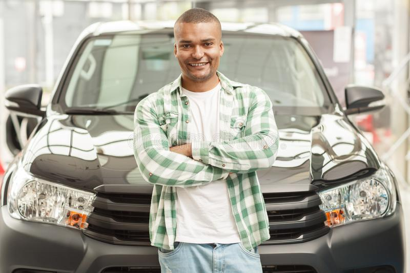 Hombre africano hermoso que elige el nuevo coche en la representación imagen de archivo