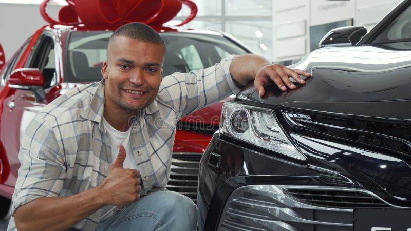 Hombre africano hermoso que muestra los pulgares para arriba mientras que examina el nuevo coche imagenes de archivo