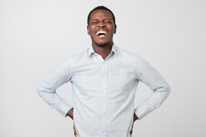 Hombre africano hermoso que ríe hacia fuera ruidosamente del meme o de la broma divertido que él encontró en Internet, sonriendo  imágenes de archivo libres de regalías