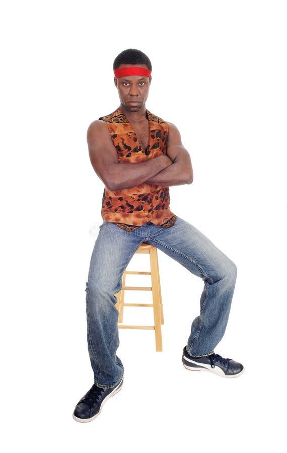 Hombre africano hermoso que se sienta en un chaleco foto de archivo