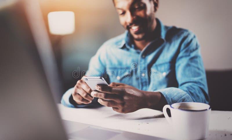 Hombre africano joven atractivo que usa smartphone mientras que sienta en la tabla de madera su hogar moderno Concepto de gente foto de archivo