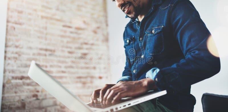 Hombre africano joven barbudo que sonríe y que usa el ordenador portátil mientras que se sienta en su lugar coworking moderno Con fotos de archivo libres de regalías