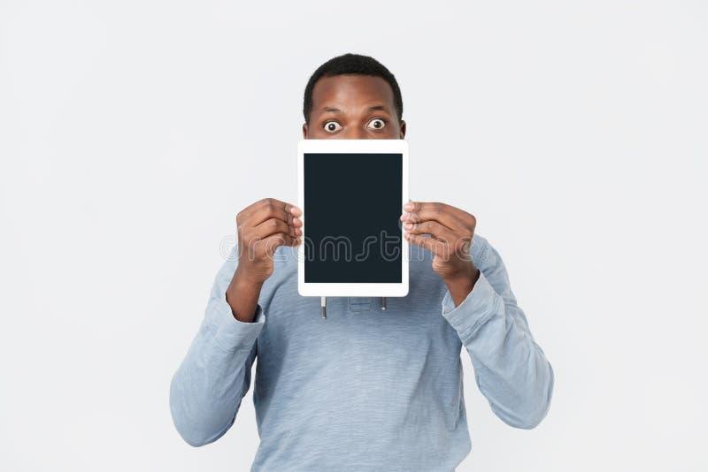 Hombre africano joven con la pantalla de la demostración de la tableta de la tableta moderna foto de archivo