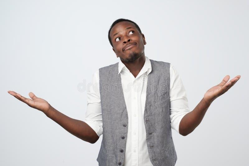 Hombre africano joven en la camisa azul que está en una pérdida, mostrando gesto desamparado con el brazo y la mano imagen de archivo