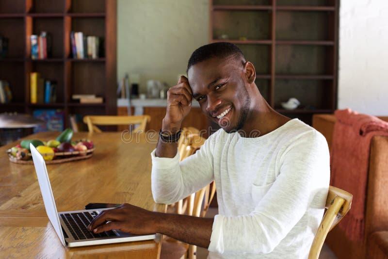 Hombre africano joven feliz que se sienta en la tabla con el ordenador portátil imagenes de archivo