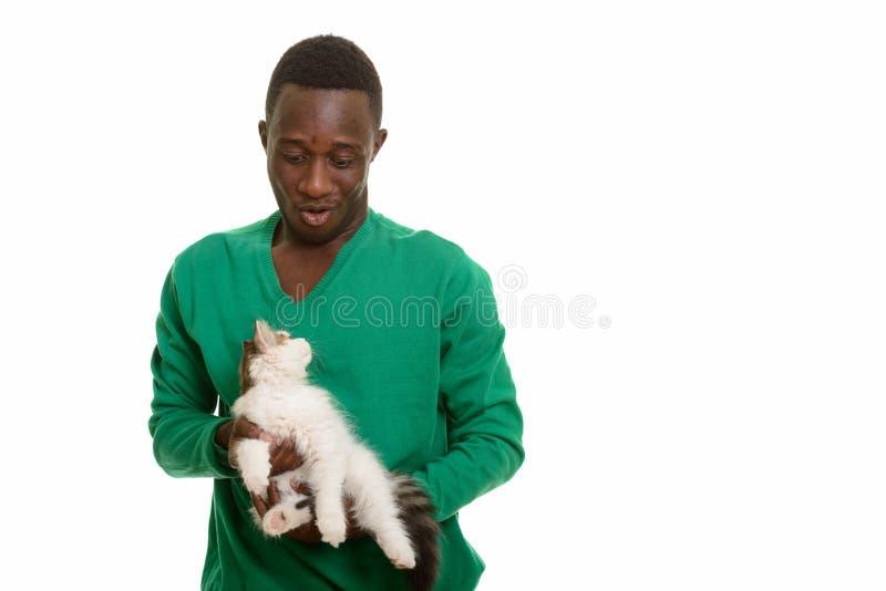 Hombre africano joven que hace la cara divertida mientras que sostiene el gato lindo foto de archivo