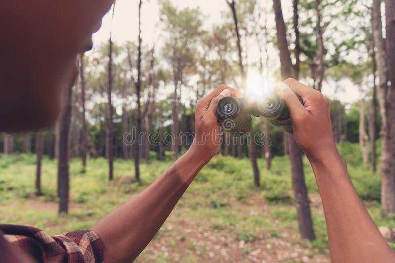Hombre africano joven que mira con binocular en el bosque, Trave imágenes de archivo libres de regalías