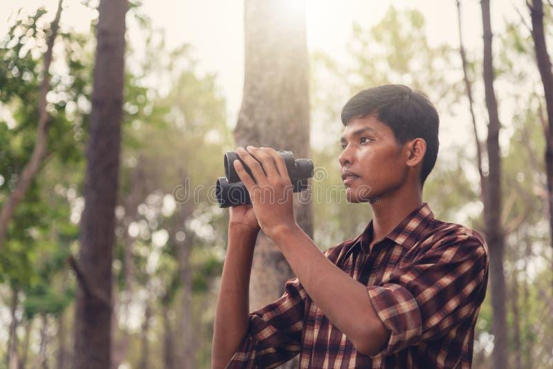 Hombre africano joven que mira con binocular en el bosque, Trave foto de archivo