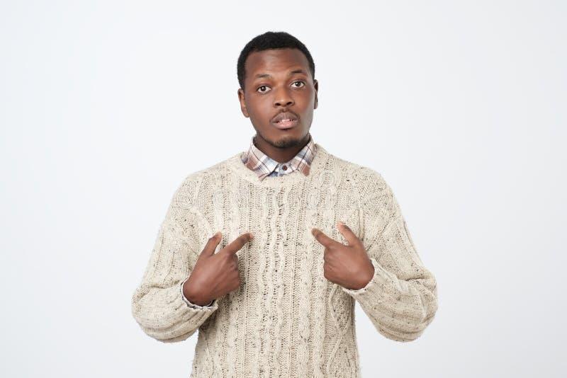 Hombre africano joven que señala en sí mismo, haciendo las excusas o verbalmente la defensa, dejando perplejo y desconcertada Exp imagen de archivo