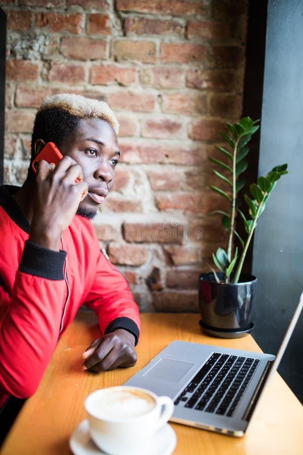 Hombre africano joven que se sienta en el teléfono móvil de la charla de cafetería Estudiante que lleva la ropa de moda, café de  fotografía de archivo