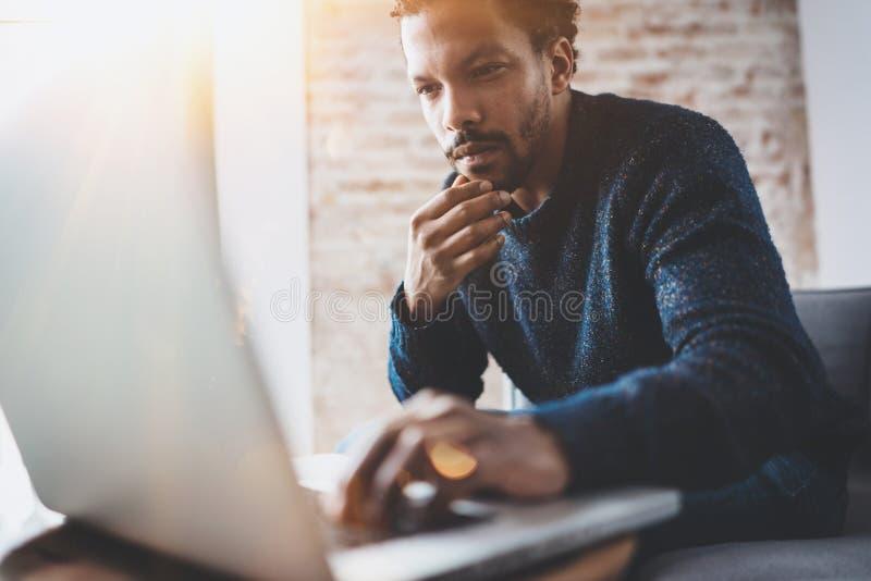 Hombre africano joven que usa el ordenador portátil mientras que se sienta en su lugar coworking moderno Concepto de hombres de n imagen de archivo