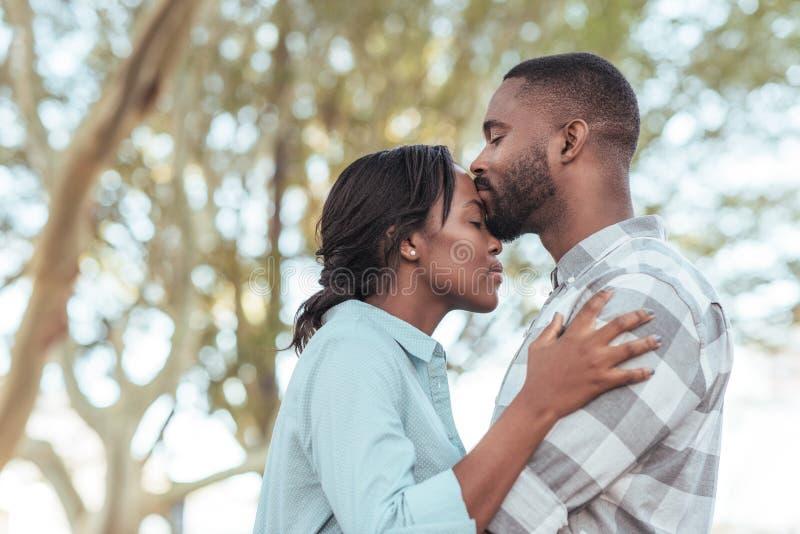 Hombre africano joven romántico que se besa la frente del ` s de la novia al aire libre foto de archivo