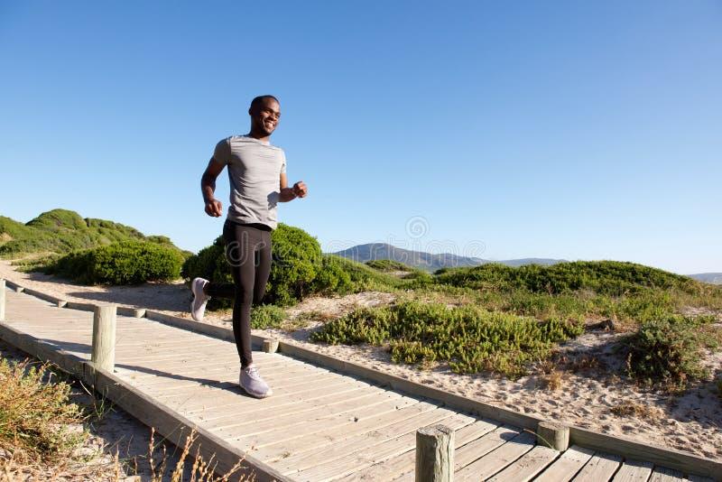 Hombre africano joven sano que corre en paseo marítimo en la playa fotos de archivo