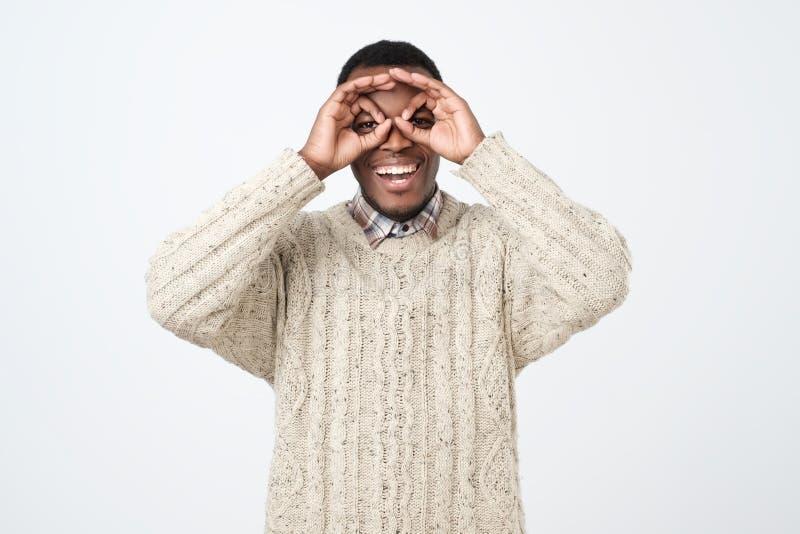 hombre africano joven, sonriendo y haciendo los prismáticos con sus manos que llevan el suéter fotos de archivo libres de regalías