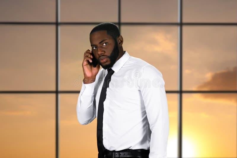 Hombre africano nervioso con el teléfono móvil imagen de archivo libre de regalías
