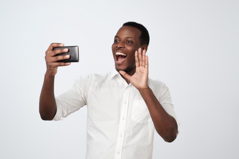 hombre africano que hace el selfie en su artilugio, electrónico, el dispositivo, sosteniendo el teléfono elegante a disposición y imágenes de archivo libres de regalías
