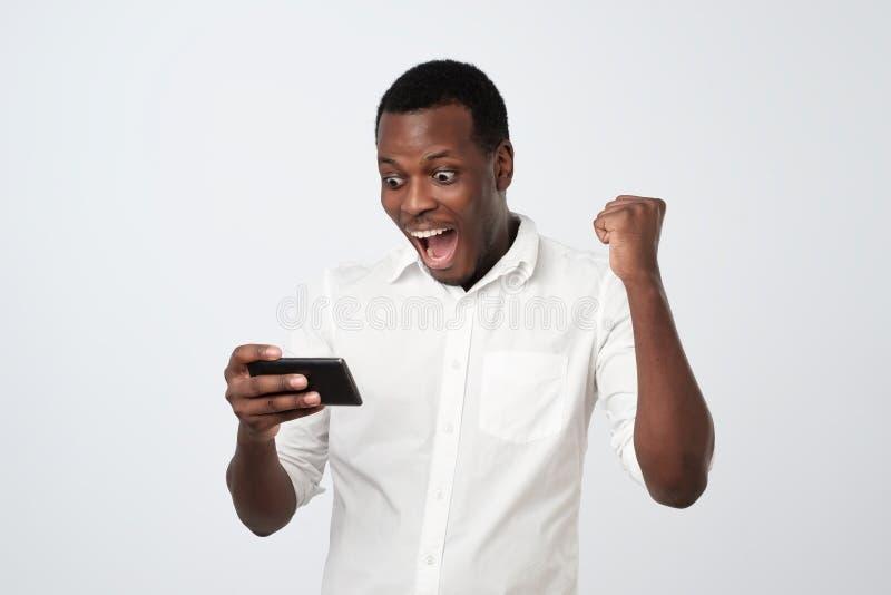 Hombre africano que juega al juego móvil con la cara chocada Consiguiendo SMS de novia con las noticias que ella está embarazada fotos de archivo