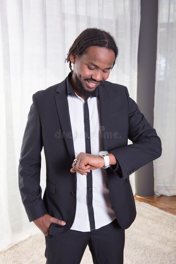 Hombre africano que mira en el reloj foto de archivo libre de regalías